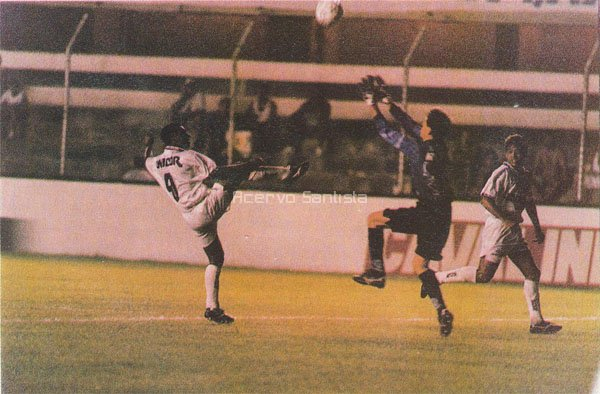 Atacante Macedo encobre goleiro Murilo do Grêmio observado pelo meia Marcelo Passos.